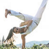 kittydesade: A woman standing on one hand, legs spread and one arm tucked in front of her chest, in mid-kick. (capoeira girl)