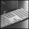 auguris: black and white photo of a keyboard and mug of hot coffee (working)