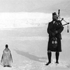 sohotrightnow: An old photograph of a bagpiper and a penguin. ([etc] an indifferent penguin)
