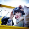 muccamukk: Phryne sitting in the cockpit of a biplane, about to pull her goggles down. (MFMM: Flying)