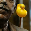 sunnymodffa: Close-up shot of a bronze and moustached statue. A yellow duckie on a stick emerges from behind his shoulder. (Duck on a Stick)