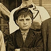 jamesmcginty: Young glass worker in Indiana, dark jacket, newsboy hat, arms crossed over his chest (James(young))