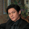 citizendamian: Joseph Marco in a dark suit and shirt looking slightly up right, seated (Damian(good?))