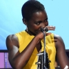 citizenmoore: Lupita Nyong'o holding her hand to her mouth in front of a mic (Yvette(amused))