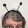 emceeaich: A woman in glasses with grey hair, from the eyes up, wearing a hairband with 'insect antenna' deelie-boppers (bugmaster)