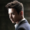 avian_cat: Won Bin, looking down left, in a dark suit with a white shirt (Default)