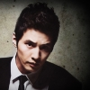avian_cat: Won Bin in harsh lighting, black suit and tie, white shirt, looking upward (Tom(stealth))