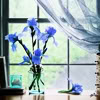 ninamalfoy: a few blue flowers in a glass vase in front of a window, spring-like coloring (blumen:strauß)