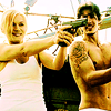 ninamalfoy: grinning Audrey Parker pointing a gun off-screen, next to her is topless!Duke looking at her (haven:bamf!audrey)