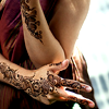taennyn: a woman's torso, left elbow and right hand visible and decorated in henna designs (wild by the roadside)