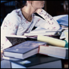 taennyn: a young woman in a white longsleeved shirt, seen among a pile of reference books (among the tools of the trade)