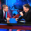 sarcasticsra: Brian Williams and Jon Stewart at the desk, Brian leans in, Jon holds a pen to his mouth and smiles (brian & jon: brian makes jon smile)
