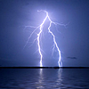 klgaffney: Lightning at night striking the far shore over otherwise calm water. (lightning on the bay.)