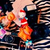 celestialdescent: Image: A collection of items, including two cameras, a Hello Kitty toy, and a handwritten note. (Default)
