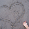 sotto_voce: A heart drawn in the sand, with a foot in the shot ([misc] hearts)