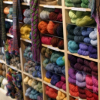 kittydesade: Several shelves neatly stacked with balls of yarn, grouped by color family. (all your yarn are belong to me)