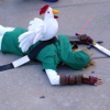 timezone: cosplay of Link from the Zelda series laying on the ground as if dead with a stuffed animal chicken on his back (Default)