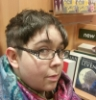 likesyew: Picture of my face from a high angle, having just cut my hair very short. Taken in a bookshop. (haircut)