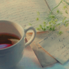 attie: A cup of tea and a green branch resting on some paper. (justpretty - cup of tea)