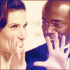 purple_smurf: Idina Menzel and Taye Diggs, Idina has her hands up in front of her face as she makes a point. (idina and taye)