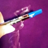 darkemeralds: Vape pen with a blue mouthpiece, cannabis cartridge attached, emitting curls of vapor (Cannabis)