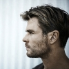 lessthanaman: Chris Hemsworth looking left with a corrugated wall behind him (stand tall)