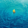 anaraine: Moana's ship is a tiny speck in the middle of the ocean, which is patterned with a design reminiscent of Maui's tattoos. ([disney] ocean blue)