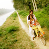 talibusorabat: An Indian man and woman ride on a bike in the countryside (Dil Bole Hadippa: Biking in paradise)