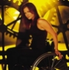 davidgillon: Dina Meyer as Oracle, sitting a manual chair in front of a clock face (Wheelchair)