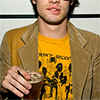 vulpines: bren wearing a yellow t-shirt and tan jacket, holding a glass of beer (reinvent love)
