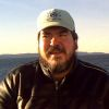 bigmacbear: Me in a leather jacket and Hockey Night in Canada ball cap, on a ferry with Puget Sound in background (closeup)