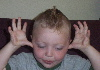 aunthippie: A young blonde child with a mohawk sticks his tongue out and waves his hands near his ears (cdawg)