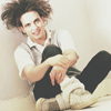 horizon_greene: Robert Smith sitting on the ground with his legs crossed, smiling. (robert socks)