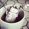 falena: a robot-shaped tea infuser peeking out of a mug (robot tea)