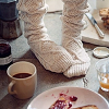 falena: female feet wearing chuncky woolen socks, next to them there is a mug of coffee or possibly tea and an empty and d plate (winter)