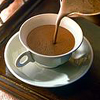 hermionesviolin: image of a white teacup on a saucer with a medium-brown liquid (hot chocolate?) being poured into it (warmth in the cold)