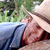 ada_hoffmann: close up on man in a straw hat hugging a dinosaur (happy - dinosaur hug)