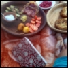 questioncurl: a platter of food and fruits, with a notebook, on a blanket (food)