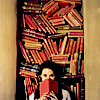 shiegra: a girl sitting in front of a packed bookshelf, shielding her face with an open book (death i think is no parenthesis)