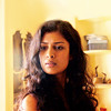 shopfront: Source: Sense8. Kala in a yellow room looking down at something (S8 - [Kala] the loveliest scientist)