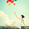 sloth: brightly coloured balloons held by a woman in white in a field (celebratory balloons!)