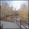 child_of_the_air: Photo of a walkway with a concrete railing, with a small river bordered by leafless trees in the background. (Default)