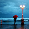 revolutions: A person with a red umbrella standing under a streetlamp by the seafront (beside the seaside)
