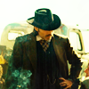 muccamukk: Doc Holliday in a swirl of smoke, coat and drama, face hidden by hat. (WE: Melodrama)