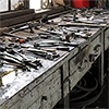 vulpines: many rusted tools sitting across a workbench. (loose bolt of a complete machine)
