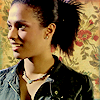 auroracloud: Martha Jones with her hair tied back and smiling, floral wallpaper-style background (Martha floral background)