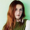 intheheart: A picture of Neko Case in a green sweater and white shirt, looking at the camera, hair loose. (Default)
