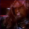 beasts_of_homeworld: large Klingon, dark brown skin. curly darker brown hair, thick wild mane down past their shoulders. fierce & intense but not unfriendly; resting, staring into distance. handsome forehead ridges remind of tiger stripes. Klingon clothes, no starfleet uniform. not quite the same Worf seen in star trek. (Worf)