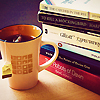slash4femme: a stack of hardcover books sits to the right of a cup of tea (Default)