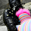 consolationsbethere: feet in black boots with stars and legs with pastel rainbow stockings (Default)